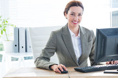 Businesswoman using computer and smiling at camera Royalty Free Stock Image