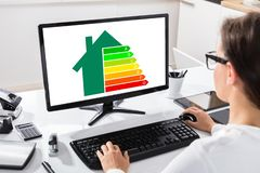 Businesswoman Using Computer With Energy Efficiency Chart. Close-up Of A Businesswoman Using Computer With Energy Efficiency Chart On Screen Over Desk stock photos