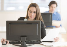 Businesswoman Using Desktop Pc At Desk Stock Image
