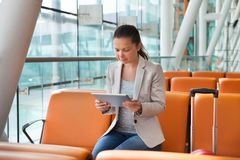Businesswoman using digital tablet at airport lobby. Young businesswoman using digital tablet while waiting for flight at airport lobby Royalty Free Stock Photography