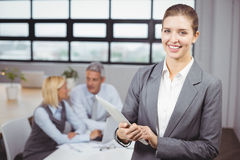 Businesswoman using digital tablet in background at office Stock Photo