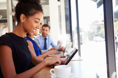 Businesswoman Using Digital Tablet In Coffee Shop Stock Images