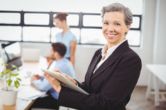 Businesswoman using digital tablet with colleagues in background. Portrait of businesswoman using digital tablet with colleagues in background at office Stock Image