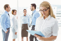 Businesswoman using digital tablet with colleagues behind Stock Photos