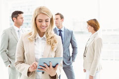 Businesswoman using digital tablet with colleagues behind Royalty Free Stock Image