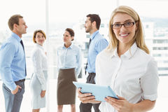 Businesswoman using digital tablet with colleagues behind Royalty Free Stock Images
