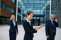 Businesswoman using digital tablet while colleagues talking on mobile phone Royalty Free Stock Photography