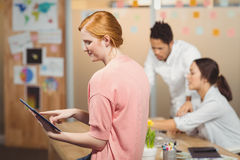 Businesswoman using digital tablet with colleagues working in office Stock Photography