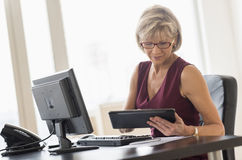 Businesswoman Using Digital Tablet At Computer Desk. Mature businesswoman using digital tablet at computer desk in office Stock Photo