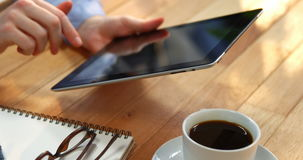 Businesswoman using digital tablet at desk with cup of coffee, spectacles and notebook on table. In office stock video footage