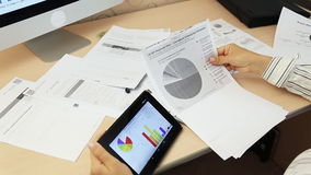 Businesswoman using digital tablet with graphs. Cropped image of businessman using digital tablet with colleagues at desk in office stock video