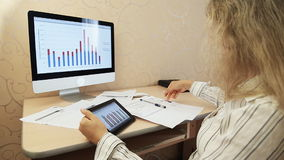 Businesswoman using digital tablet with graphs. Cropped image of businessman using digital tablet with colleagues at desk in office stock footage