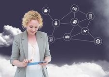 Businesswoman using digital tablet with networking icons and cloud in background. Digital composition of businesswoman using digital tablet with networking icons Stock Image