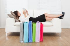 Businesswoman using digital tablet with shopping bags on floor Stock Images