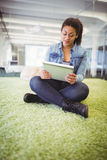 Businesswoman using digital tablet while sitting on carpet in creative office Royalty Free Stock Image
