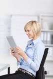 Businesswoman Using Digital Tablet While Sitting On Chair In Off Royalty Free Stock Images