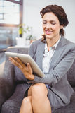 Businesswoman using digital tablet while sitting in office Royalty Free Stock Photo