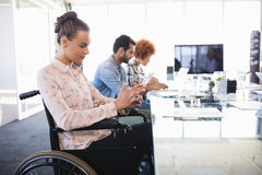 Businesswoman using digital tablet while sitting on wheelchair Royalty Free Stock Photo