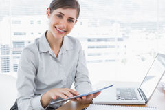 Businesswoman using digital tablet smiling at camera Stock Image