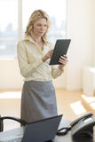 Businesswoman Using Digital Tablet While Standing By Desk Royalty Free Stock Photography