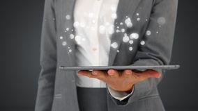 Businesswoman using digital tablet surrounded by white bubbles effect. Digital composite of businesswoman using digital tablet surrounded by an animation of stock video footage