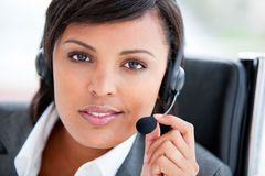 Businesswoman using earpiece sitting in her office Royalty Free Stock Photo