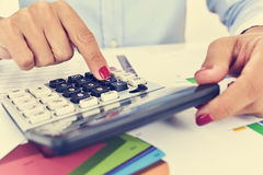 Businesswoman using an electronic calculator in her office Royalty Free Stock Images