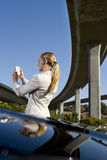 Businesswoman using electronic organiser by car beneath overpass, low angle view Stock Image