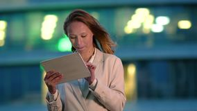 Businesswoman using electronic tab outdoors in the evening.