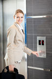 Businesswoman using elevator Stock Images