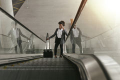 Businesswoman using escalator at airport terminal. And holding smartphone Stock Photo