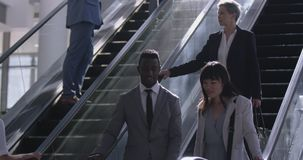Businesswoman using escalator in a modern office 4k. Front view of diverse businesswoman using escalator in a modern office. They are smiling 4k stock footage