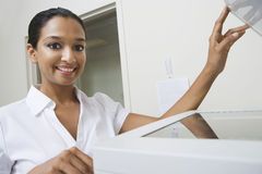 Businesswoman Using Fax Machine In Office. Portrait of a happy businesswoman using fax machine in office stock images