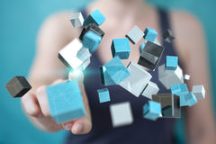 Businesswoman using floating blue shiny cube network 3D renderin. Businesswoman on blurred background using floating blue shiny cube network 3D rendering Royalty Free Stock Photography
