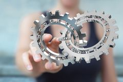 Businesswoman using floating modern gear mechanism 3D rendering. Businesswoman on blurred background using floating gear icons 3D rendering Royalty Free Stock Photo