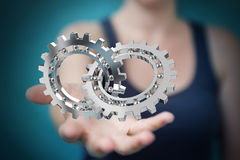 Businesswoman using floating modern gear mechanism 3D rendering. Businesswoman on blurred background using floating gear icons 3D rendering Royalty Free Stock Image