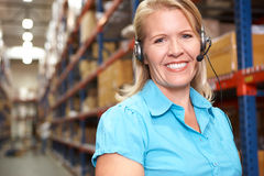 Businesswoman Using Headset In Distribution Warehouse. Smiling stock photo