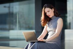 Businesswoman using her laptop computer in a modern office build Royalty Free Stock Photos