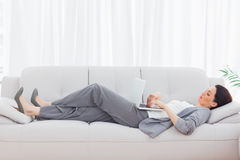 Businesswoman using her laptop lying on sofa Stock Photos