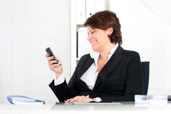 Businesswoman using her mobile at work Stock Photography