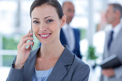 Businesswoman using her phone with two colleague behind her Stock Image