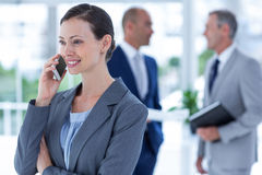 businesswoman using her phone with two colleague behind her Stock Photo