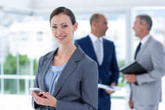 Businesswoman using her phone with two colleague behind her Royalty Free Stock Photo