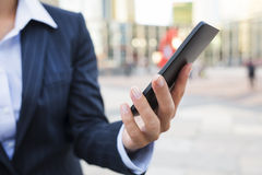 Businesswoman using her smart phone in front of Building Stock Photo