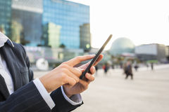 Businesswoman using her smart phone in working environment Stock Photos