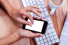Businesswoman using her smartphone on desk Stock Image