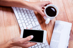 Businesswoman using her smartphone on desk Royalty Free Stock Image