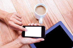 Businesswoman using her smartphone on desk Royalty Free Stock Images