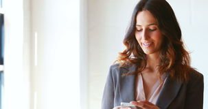 Businesswoman using her smartphone at work stock video