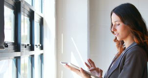 Businesswoman using her tablet by the window stock footage